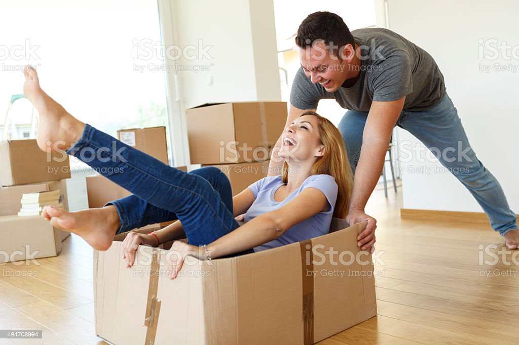 Young couple having fun while they moving into new home stock photo