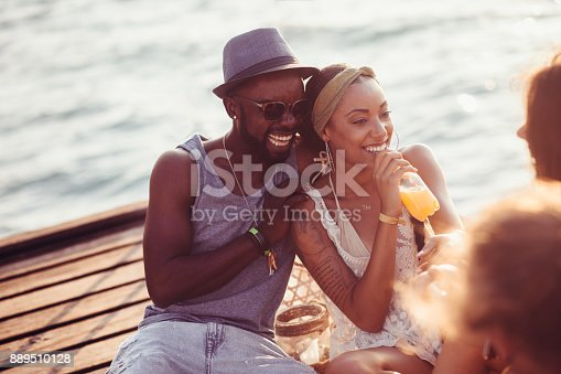 istock Young couple having fun with friends on jetty in summer 889510128