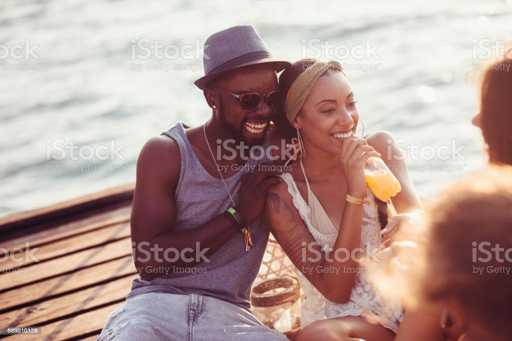 Young couple having fun with friends on jetty in summer stock photo
