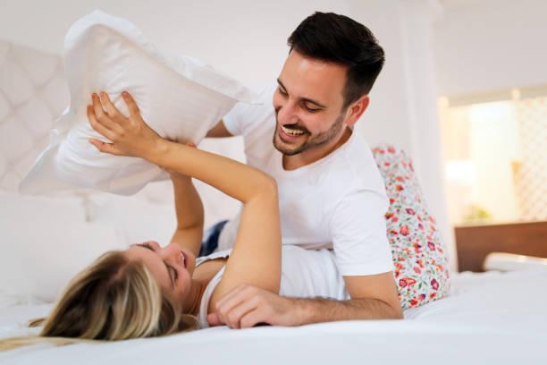 junge paare, die haben mit romantischen zeiten in schlafzimmer - kissenschlacht paar stock-fotos und bilder