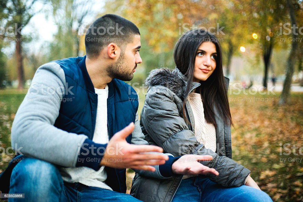 Young couple having love fight in park