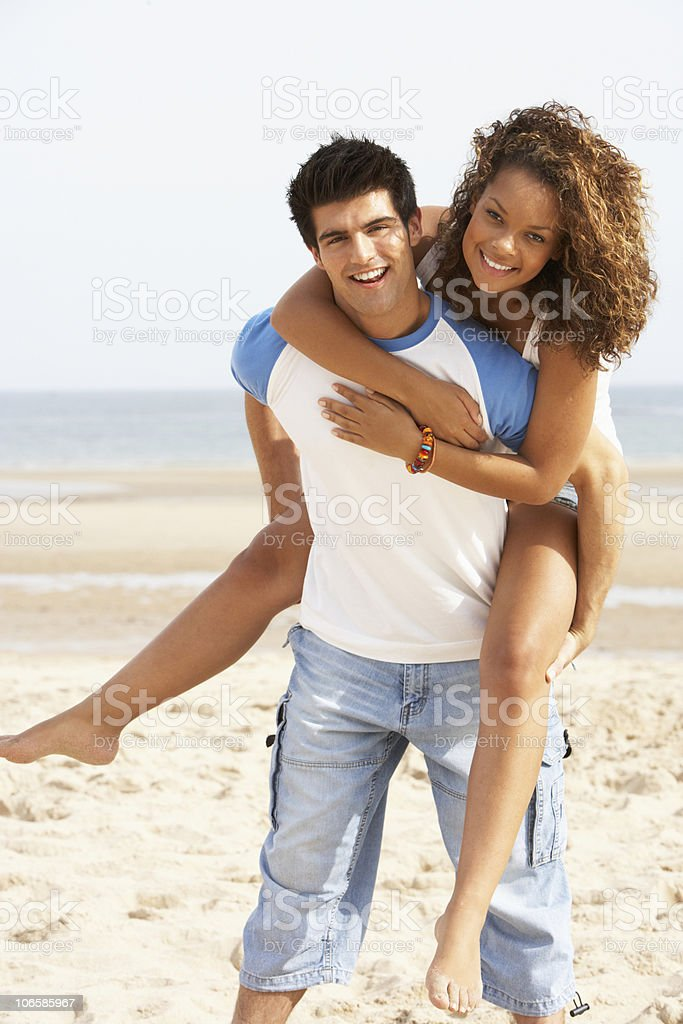 Young Couple Having Piggyback Fun On Beach stock photo