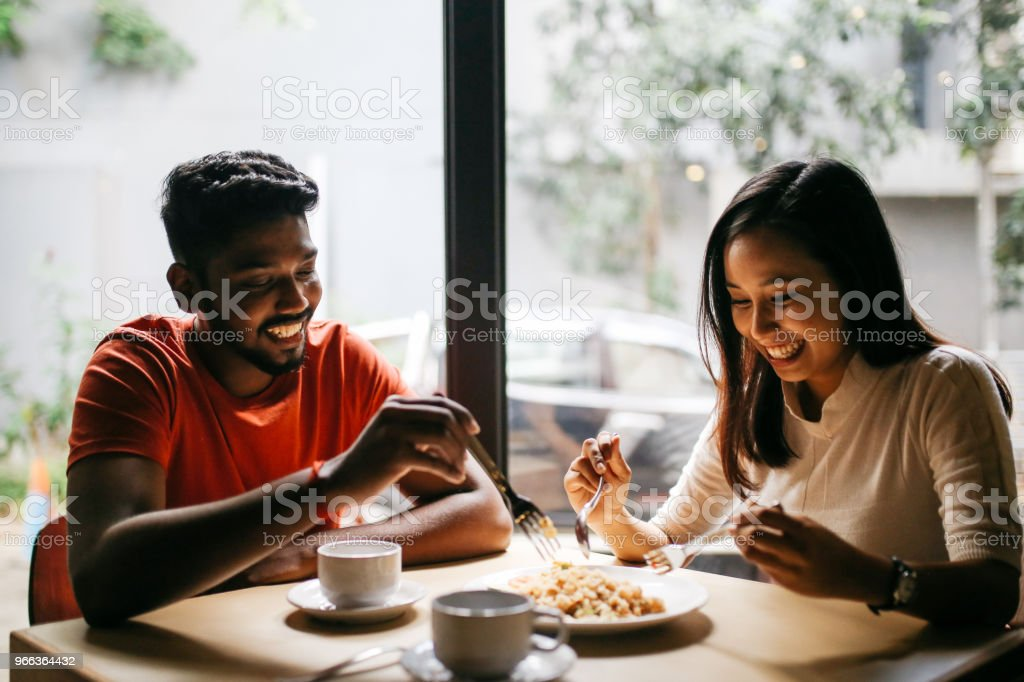 Young couple having pizza together Young couple having a pizza together in a restaurant in central Kuala Lumpur. Adult Stock Photo