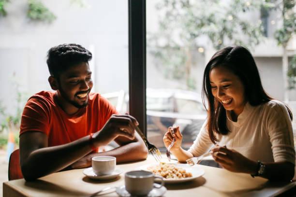 young couple having pizza together - incontro romantico foto e immagini stock