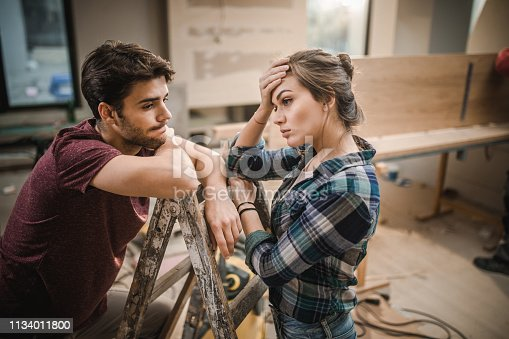 Worried couple standing on ladders and thinking the easiest way possible for home renovation.