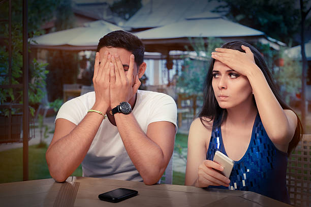 Young Couple Having Problems with Their Smart Phones Young adult couple with smart phones upset out on a date bad date stock pictures, royalty-free photos & images