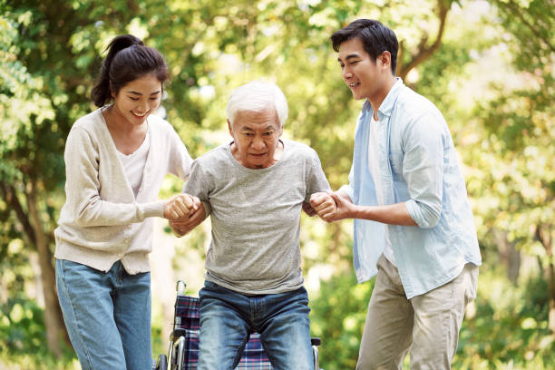 young couple helping dad stand up from wheelchair stock photo