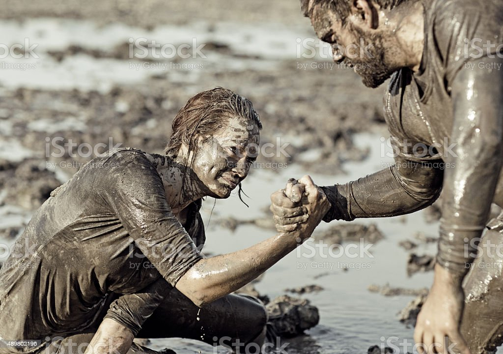 Young couple helping each other during a mud run stock photo