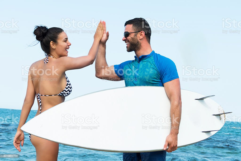 Young couple high fiving at the beach stock photo