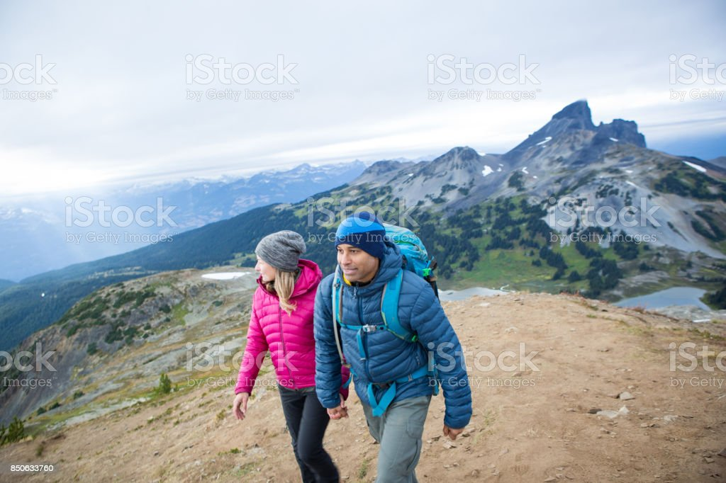 Young couple hike to the top of the mountain stock photo