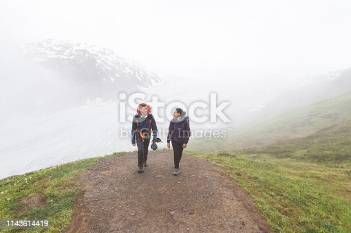 A backpacking couple in their 20s hike up a gorgeous Alaskan glacier in the fog. They are on a rocky footpath surrounded by grass and rocks. A mountain is visible through fog in the background.