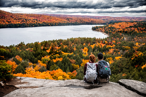 istock Young couple hiking in mountain and relaxing looking at view 621242410