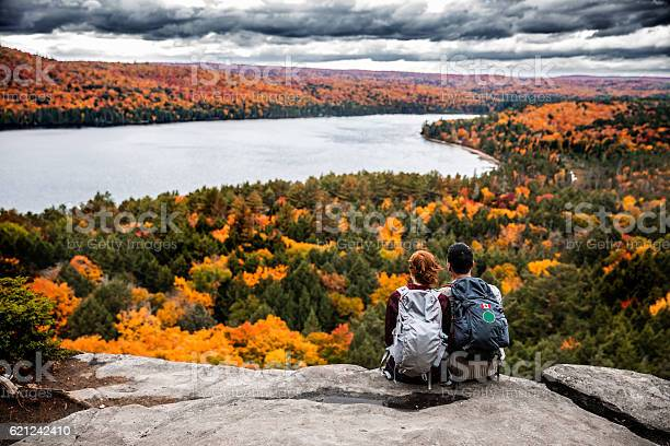 Photo of Young couple hiking in mountain and relaxing looking at view
