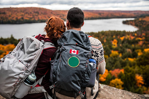 young couple hiking in mountain and relaxing looking at view - voyages au canada photos et images de collection