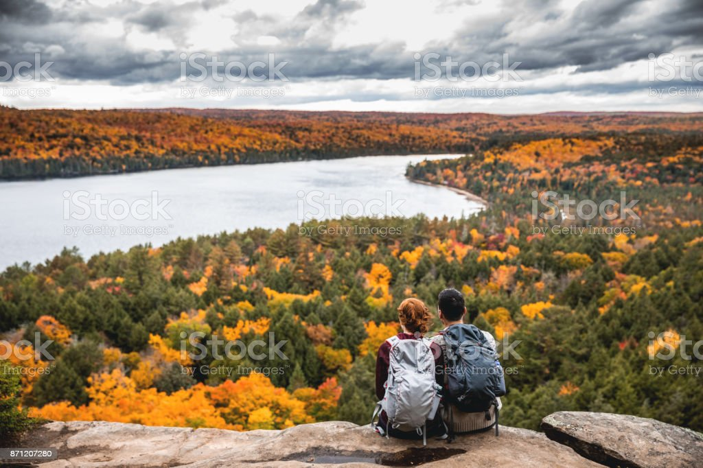 Young couple hiking in mountain and relaxing looking at view stock photo