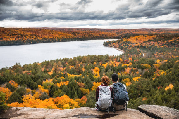 young couple hiking in mountain and relaxing looking at view - canada travel stock photos and pictures