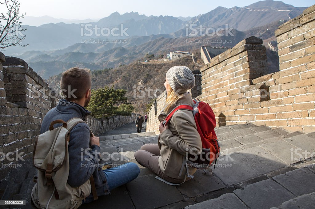 Young couple hiking the Great Wall looking at spectacular landscape-China stock photo