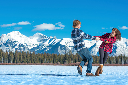 Young couple hold hands and swing on icy pond