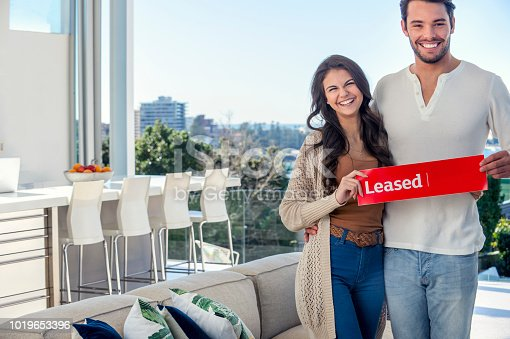 Young couple holding a leased rental sign in a luxury home. They are standing in the living room, with a view of Sydney harbour in the background. They are both happy and smiling. There is space for a real estate agents name on the sign