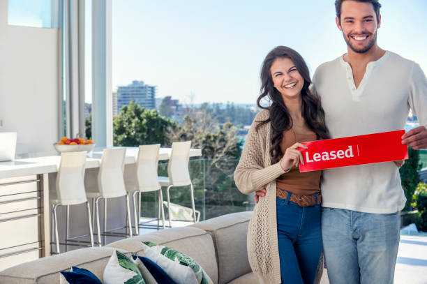 young couple holding a leased rental sign in a luxury home. - tenant stock photos and pictures