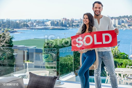 Young couple holding a sold sign in a luxury home. They are standing in the living room, with a view of Sydney harbour in the background. They are both happy and smiling.