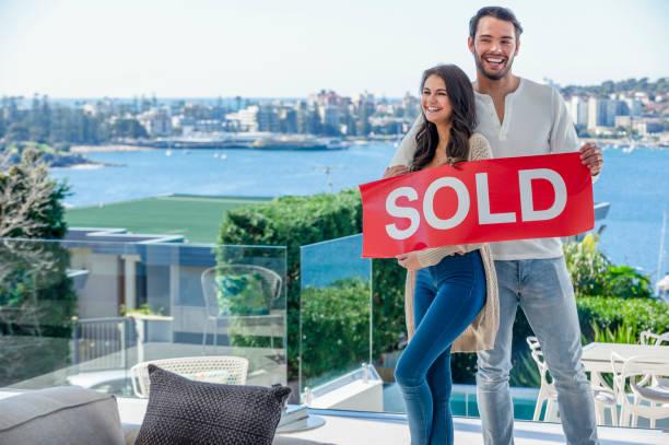 Junges Paar mit einem verkauften Schild in einem Luxus-Haus. – Foto