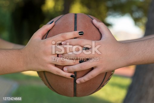 Two young men hold a basketball. Cooperation.