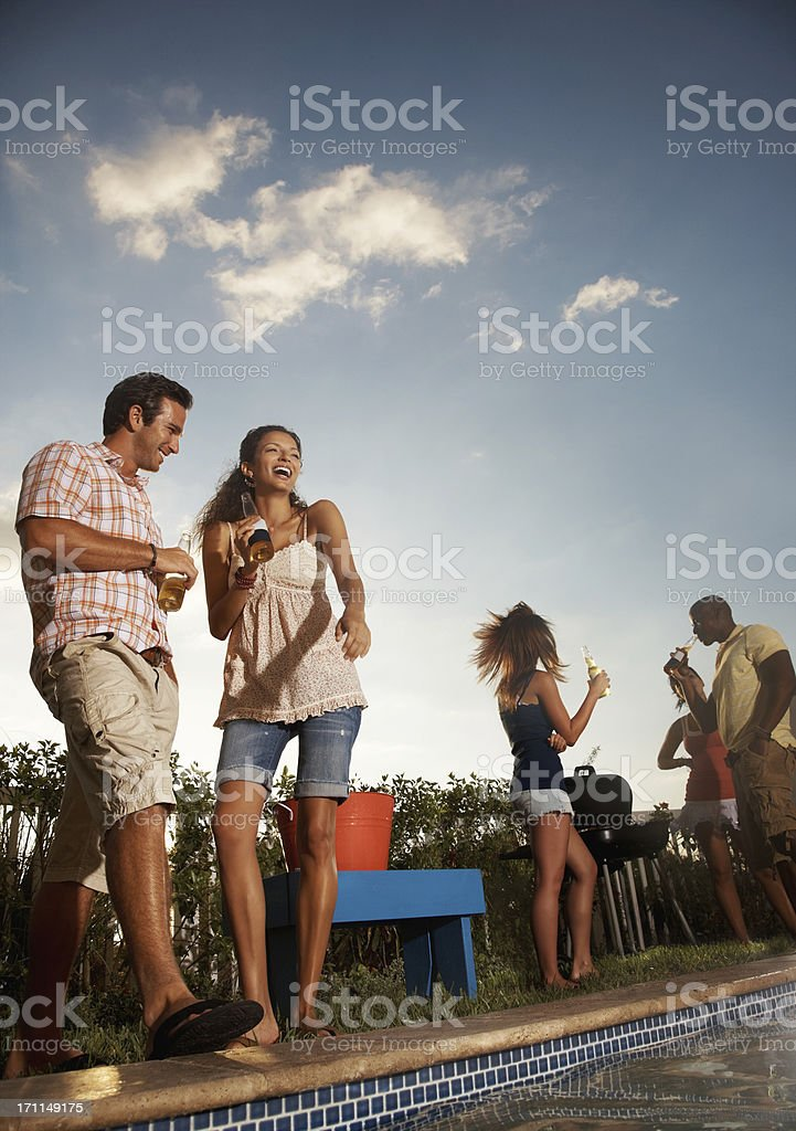 Young couple holding beer bottle with friends in background stock photo