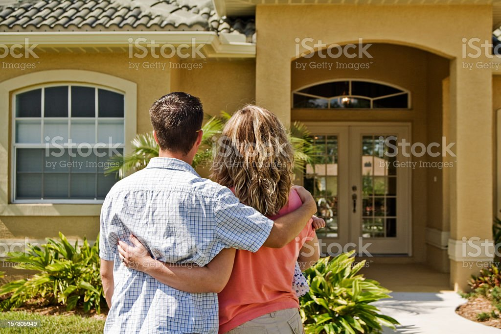 Young couple holding each other in front of a house stock photo