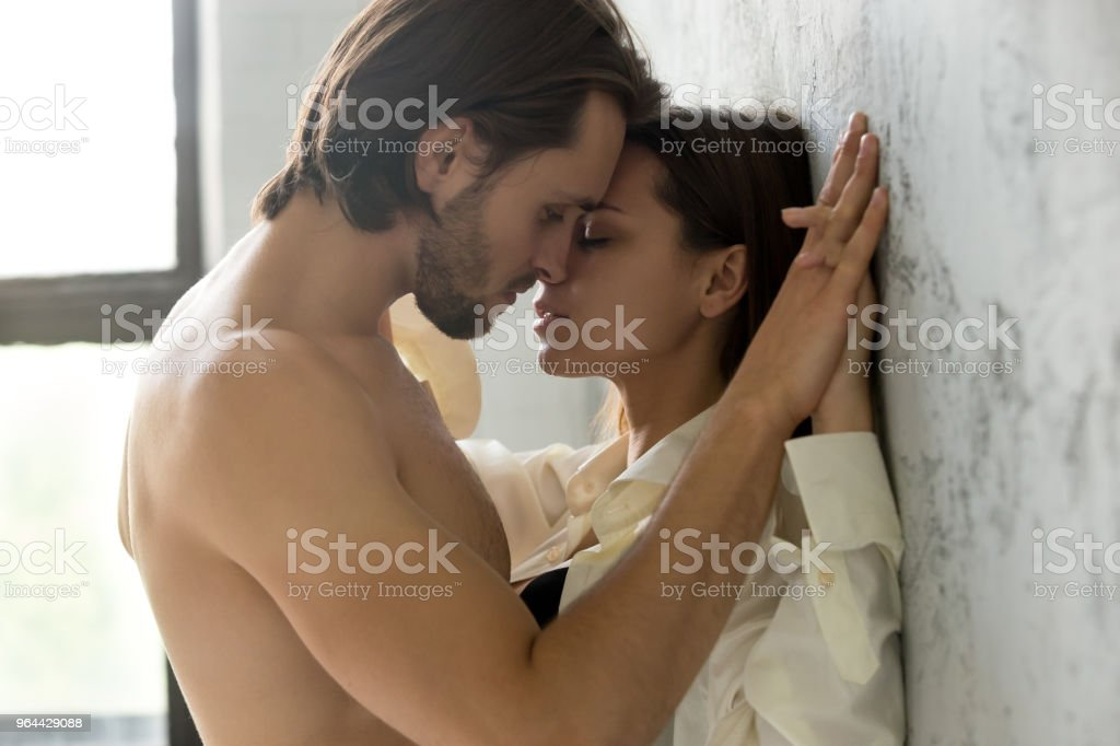 Young couple holding hands about to kiss leaning on wall stock photo