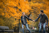 Smiling couple roller skating together in nature during autumn.