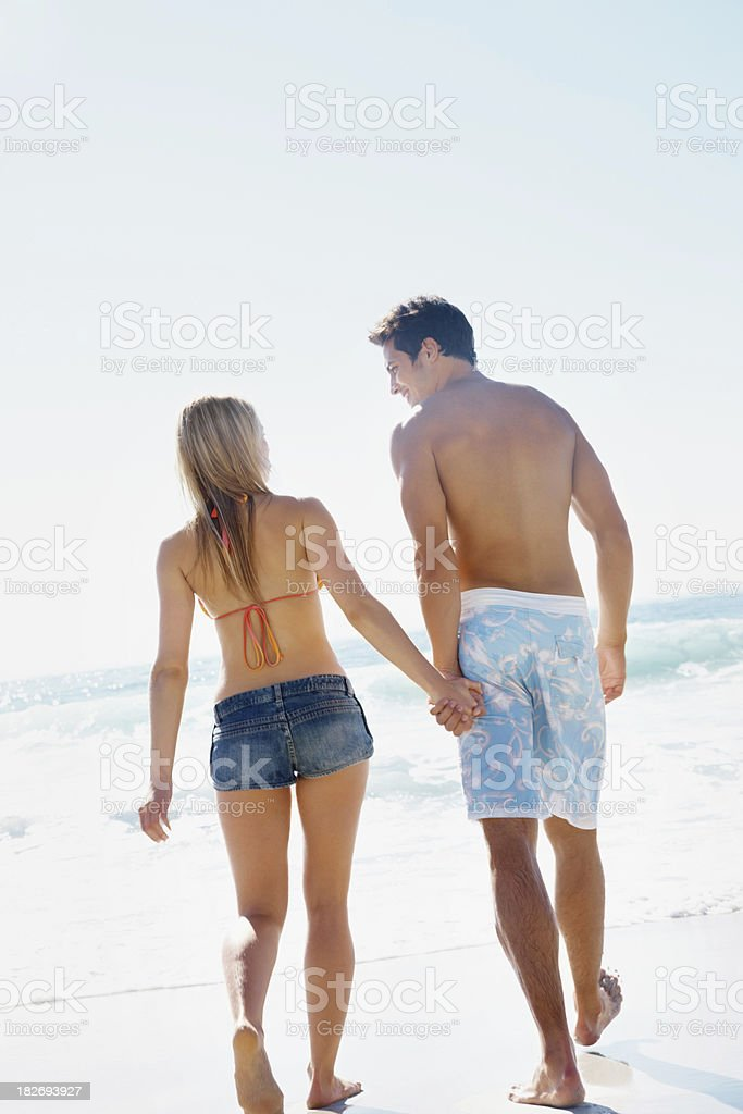 Young couple holding hands and walking on beach royalty-free stock photo