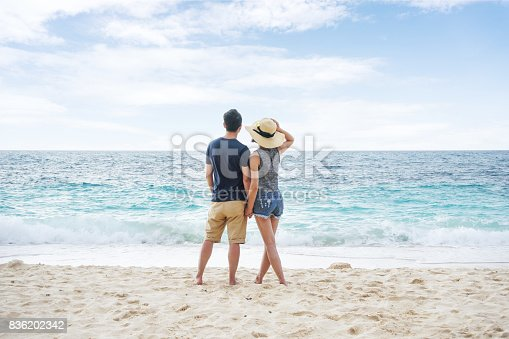 istock Young couple holding hands and walking on beach 836202342