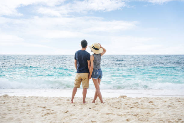 Young couple holding hands and walking on beach stock photo