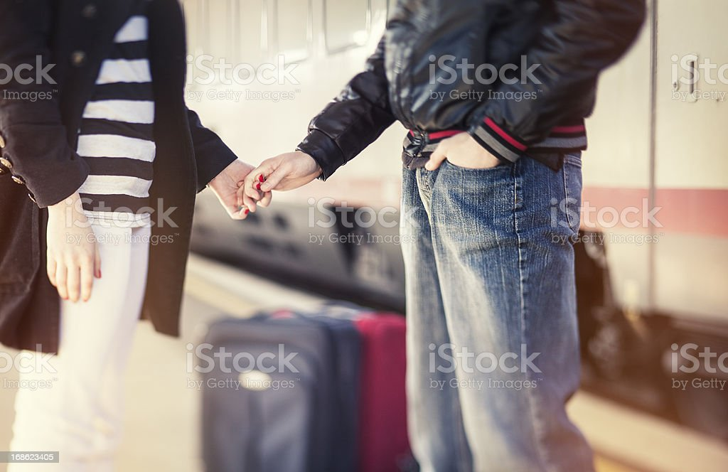 Young couple holding hands at train station stock photo