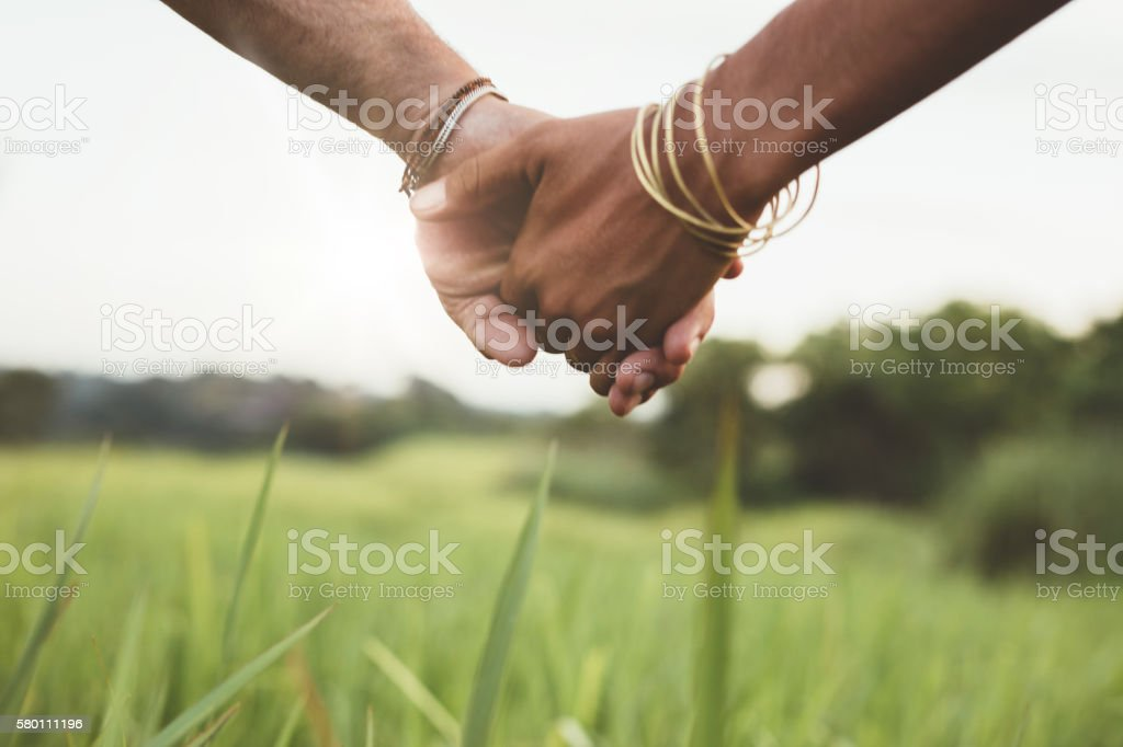 Young couple holding hands in the field stock photo