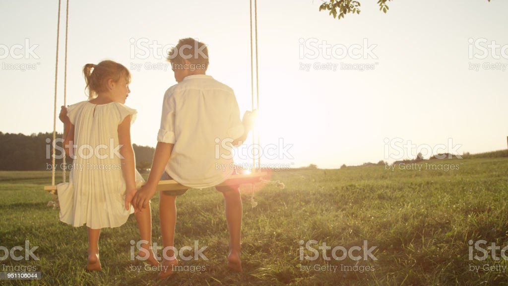 COPY SPACE: Young couple holding hands on swing at golden sunset stock photo