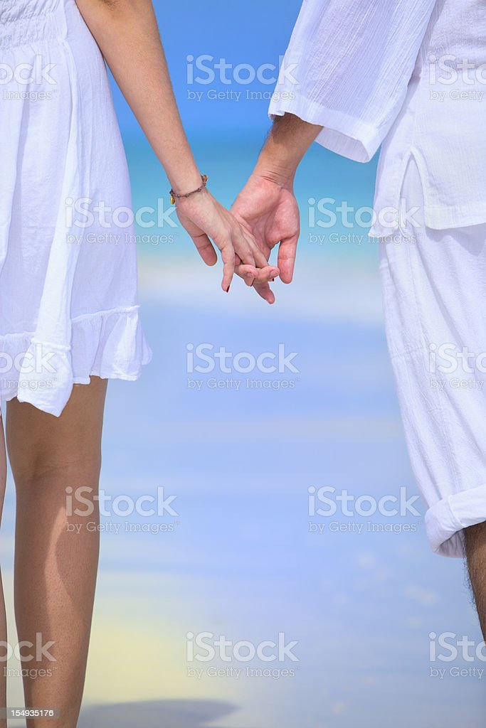 Young couple holding hands on turquoise white sand tropical beach royalty-free stock photo