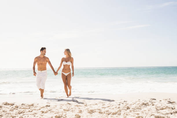 Young couple holding hands Young couple holding hands on the beach swimwear stock pictures, royalty-free photos & images