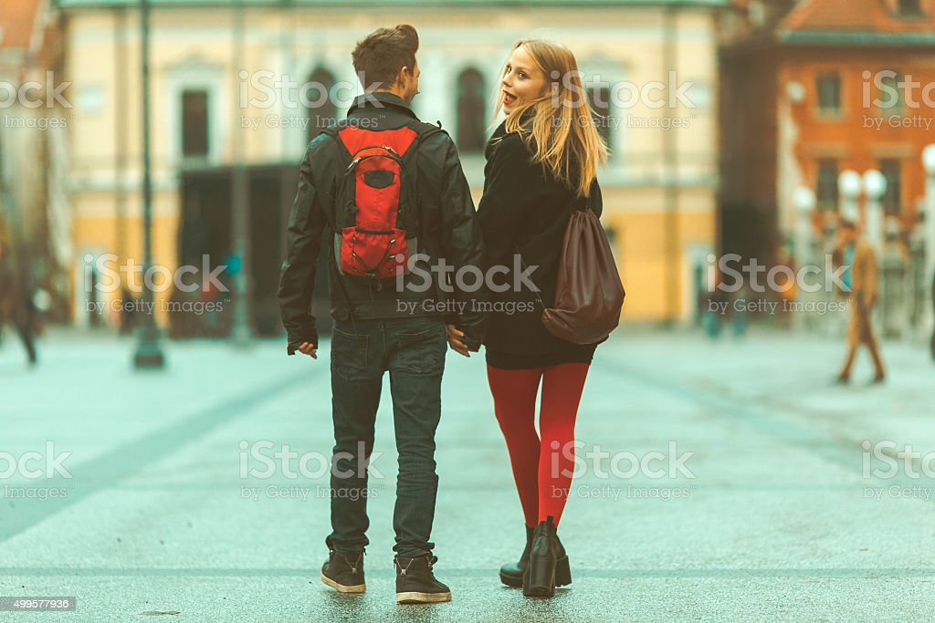 Young couple holding hands, walking in the city stock photo