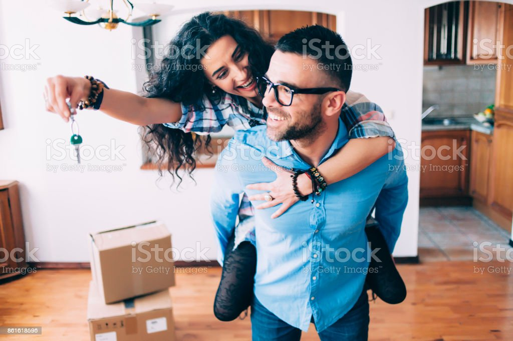 Young couple holding keys of new apartment stock photo