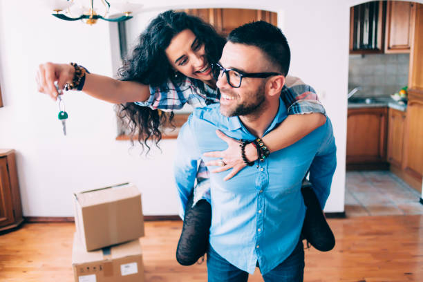 young couple holding keys of new apartment - house hunting stock photos and pictures