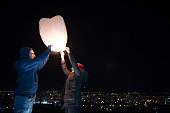 Young couple holding lantern with fire before to let it fly
