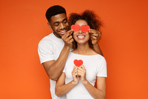istock Young couple holding red love hearts over eyes 1143286306