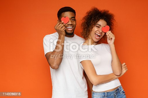 istock Young couple holding red love hearts over eyes 1143286315