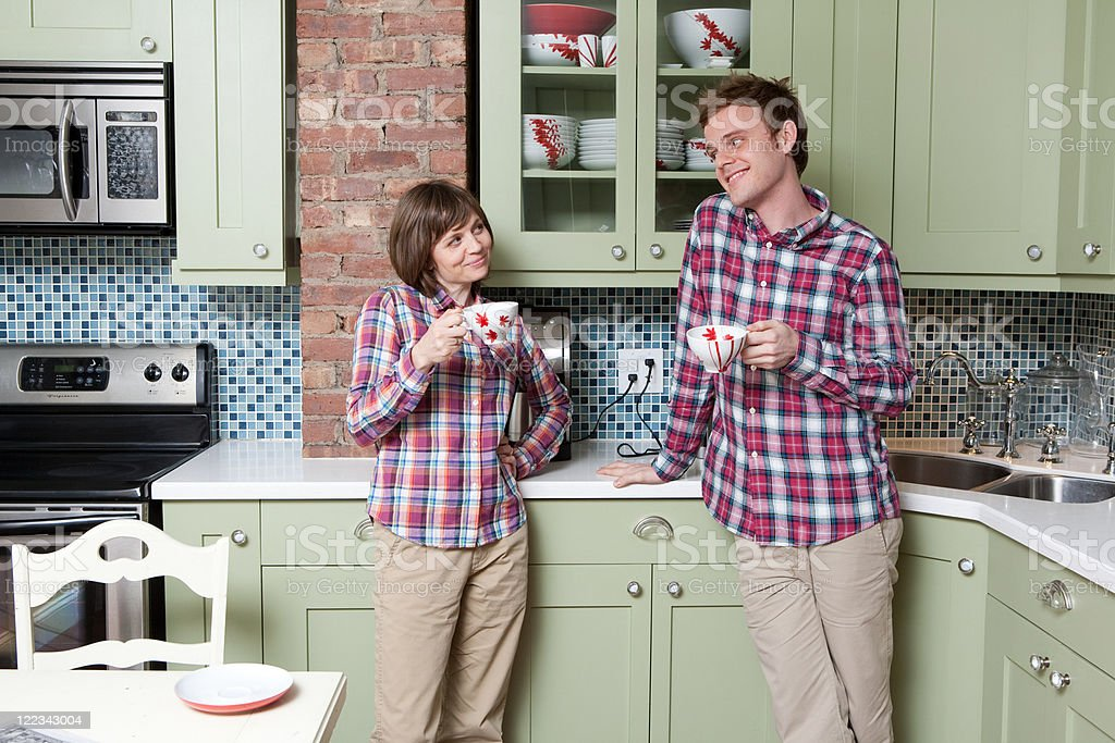 Young couple holding teacups in kitchen stock photo
