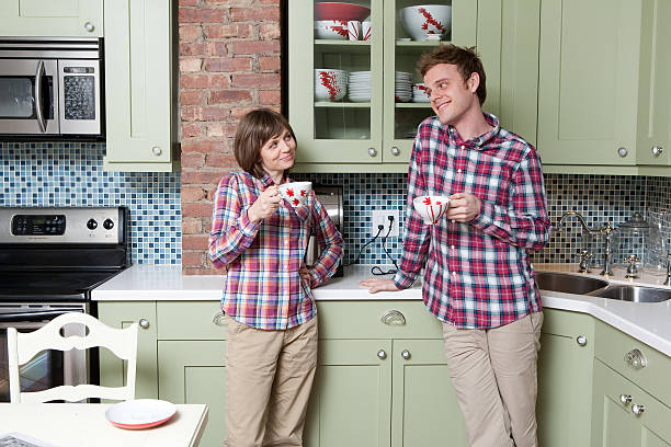 Young couple holding teacups in kitchen  plaid shirt stock pictures, royalty-free photos & images