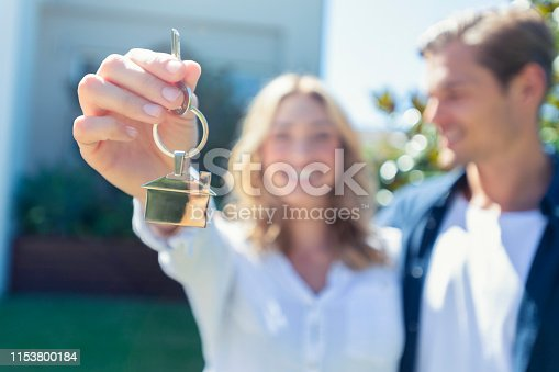 Young couple holding the key to their new house. She is smiling and happy. They keyring is shaped like a house. The house can be seen in the background. Shalloe focus