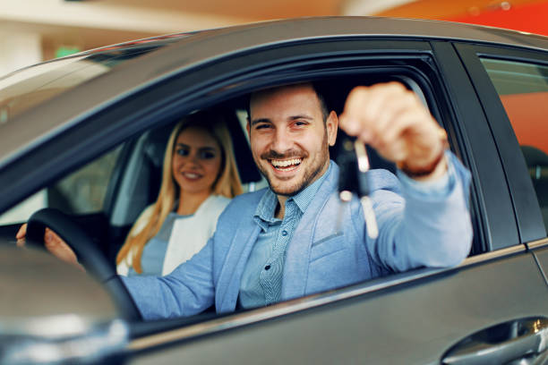 young couple holding the keys of a new car - new stock photos and pictures