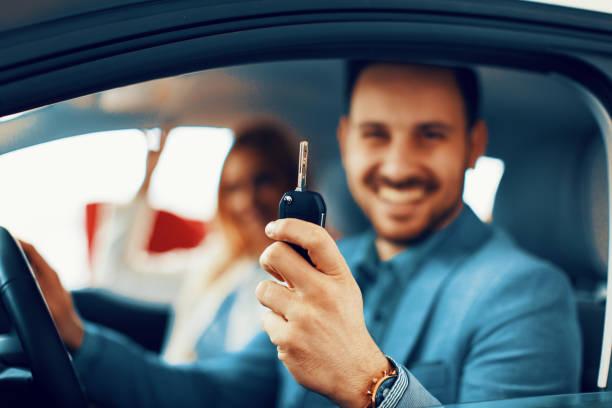 Junges Paar hält den Schlüssel für ein neues Auto. Selektiven Fokus auf Tasten – Foto
